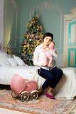 Madre feliz en sitio de la Navidad con un cochecito de niño Fotos de archivo