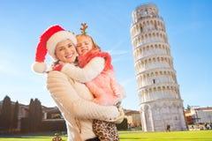 Madre feliz en sombrero de la Navidad con la hija en Pisa, Italia Foto de archivo libre de regalías