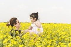 Madre feliz joven con su ni?a en la familia de la granja del canola que se divierte junto en campo del canola foto de archivo libre de regalías