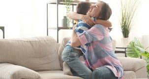 Madre feliz que abraza al hijo en casa almacen de video