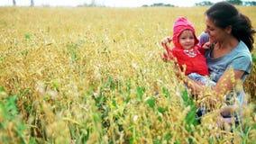 Madre feliz que abraza al niño sonriente en el campo con trigo metrajes