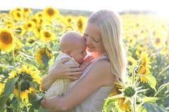 Madre feliz que abraza a la hija del bebé en prado de la flor Foto de archivo