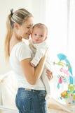 Madre feliz que abraza sus 3 meses del bebé en la ventana grande en bedr Imagen de archivo libre de regalías