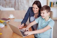Madre feliz que ayuda a su hijo a hacer la preparación Foto de archivo