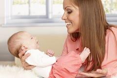 Madre feliz que celebra al bebé minúsculo Fotografía de archivo