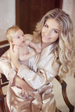 Madre feliz que celebra a su bebé recién nacido Mamá que juega con recién nacido Foto de archivo