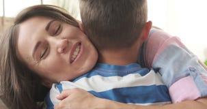 Madre feliz que da abrazo apretado a su hijo metrajes