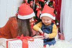 Madre feliz que da al regalo de la Navidad del bebé Foto de archivo libre de regalías