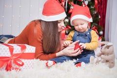 Madre feliz que da al regalo de la Navidad del bebé Imágenes de archivo libres de regalías