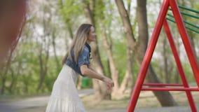 Madre feliz que empuja riendo a dos hijos en el oscilación en un parque Reconstrucci?n al aire libre almacen de video
