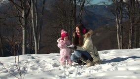 Madre feliz que juega bolas de nieve con su hija almacen de video
