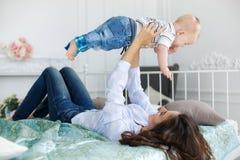 Madre feliz que juega con el bebé que miente en cama en casa Imagenes de archivo