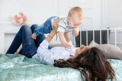 Madre feliz que juega con el bebé que miente en cama en casa Fotos de archivo
