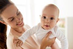 Madre feliz que juega con el pequeño bebé en casa imagen de archivo