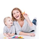 Madre feliz que juega con la mentira del pequeño niño. Fotos de archivo libres de regalías