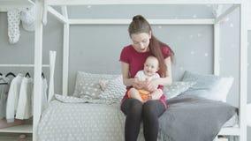 Madre feliz que juega las palmas con el bebé en casa almacen de video