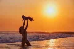 Madre feliz que lanza encima de alto del hijo del bebé en cielo de la puesta del sol fotos de archivo libres de regalías
