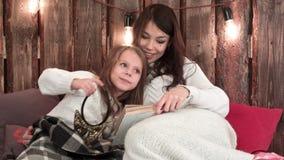 Madre feliz que lee un libro con su pequeña hija que se acurruca abajo con las mantas en un sofá metrajes