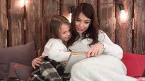 Madre feliz que lee un libro con su pequeña hija que se acurruca abajo con las mantas en un sofá Fotos de archivo