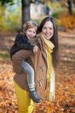 Madre feliz que lleva a cuestas a su hijo en otoño Imágenes de archivo libres de regalías