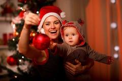 Madre feliz que muestra la bola de la Navidad al bebé Imagenes de archivo