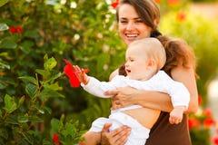 Madre feliz que muestra la flor a su bebé en la calle Fotos de archivo libres de regalías