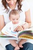 Madre feliz que muestra un libro a su bebé en el sofá Imágenes de archivo libres de regalías