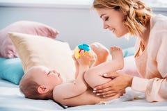 madre feliz que pone el pañal en poco niño fotos de archivo