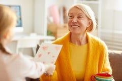 Madre feliz que recibe la tarjeta fotografía de archivo