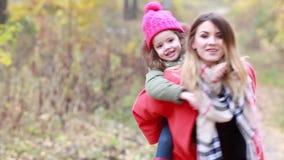 Madre feliz que retiene a su hija en ella en el parque en otoño almacen de video
