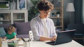 Madre feliz que trabaja en casa con el ordenador portátil que mecanografía mientras que pequeño dibujo del hijo del muchacho almacen de video