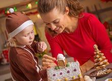 Madre feliz y bebé que adornan la casa de la galleta de la Navidad Foto de archivo libre de regalías