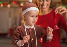 Madre feliz y bebé que juegan con las campanas de la Navidad Fotos de archivo libres de regalías