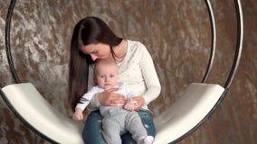 Madre feliz y beb? que se besan y que abrazan, familia feliz hermosa de la maternidad de maternidad del concepto en un oscilaci?n almacen de metraje de vídeo