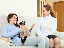 Madre feliz y cotilleo adolescente de la hija en el sofá Imágenes de archivo libres de regalías