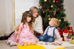 Madre feliz y dos sus niños en la Navidad foto de archivo libre de regalías