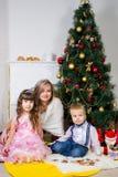 Madre feliz y dos sus niños en la Navidad fotos de archivo