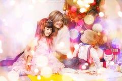Madre feliz y dos sus niños en la Navidad imagen de archivo libre de regalías