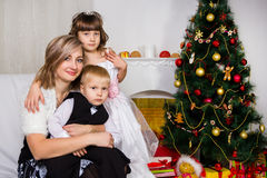 Madre feliz y dos sus niños en la Navidad foto de archivo