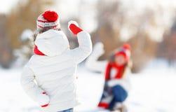 Madre feliz y niño de la familia que juegan bolas de nieve en paseo del invierno Imágenes de archivo libres de regalías