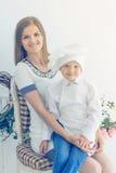 Madre feliz y niño joven bajo la forma de cocinero Fotos de archivo libres de regalías