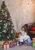 Madre feliz y niño que adornan un árbol de navidad Imágenes de archivo libres de regalías
