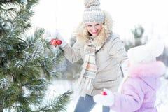 Madre feliz y niño que juegan con el árbol de navidad Imágenes de archivo libres de regalías