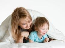 Madre feliz y niño que juegan debajo de una manta Fotografía de archivo libre de regalías