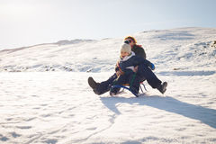 Madre feliz y niño que juegan en la nieve con un trineo Imagen de archivo libre de regalías