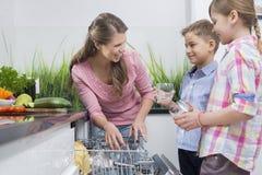 Madre feliz y niños que colocan los vidrios en lavaplatos Imagenes de archivo