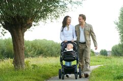 Madre feliz y padre que caminan con el bebé en cochecito de niño Fotografía de archivo