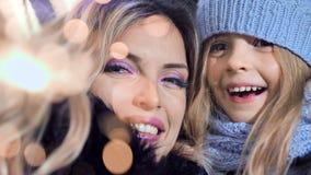 Madre feliz y pequeña hija bonita que tienen buen tiempo junto que disfruta de día de fiesta de la Navidad con las bengalas del f almacen de video
