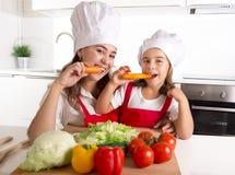Madre feliz y pequeña hija en sombrero del delantal y del cocinero que comen las zanahorias junto que tienen cocina de la diversi Fotos de archivo libres de regalías