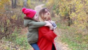 Madre feliz y pequeña hija en un paseo por la tarde del otoño metrajes